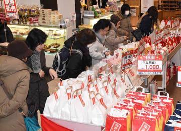 菓子や茶、レトルト食品など食料品が詰められた福袋を品定めする買い物客=1日午前11時すぎ、青森市の中三青森本店