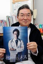 ドラマ「孤高のメス」のパンフレットを手にする大鐘稔彦さん=南あわじ市阿那賀、阿那賀診療所