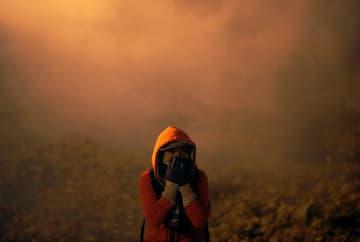 メキシコ・ティフアナの米国との国境地帯で、米当局が使用した催涙ガスに顔を覆う移民=1日(ロイター=共同)