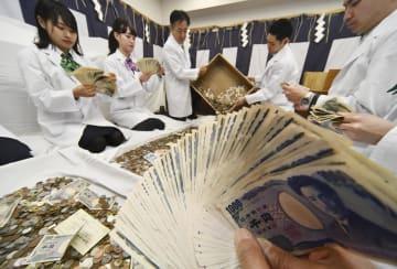 京都市の伏見稲荷大社で、正月三が日のさい銭を勘定する銀行員=4日午前