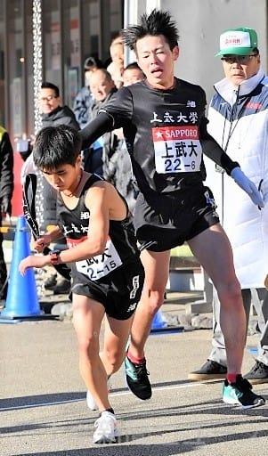 上武大の6区佐々木(右)からたすきを受けて走りだす7区坂本=神奈川・小田原中継所