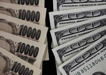 一万円札と百ドル紙幣(ロイター=共同)