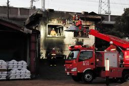 全焼した民家を調べる消防隊員ら=4日午前6時56分、神戸市西区森友5