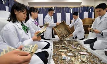 初詣の参拝者が納めたさい銭を数える銀行員たち(4日午前9時5分、京都市伏見区・伏見稲荷大社)