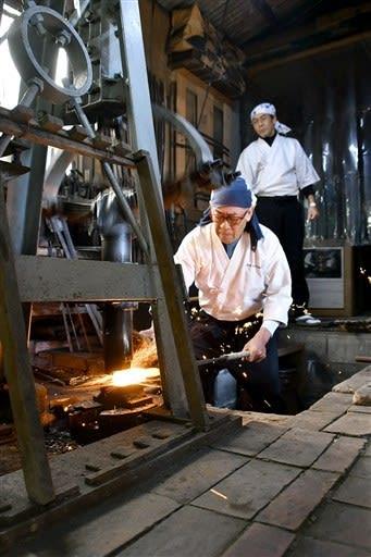 打ち初めで玉鋼を鍛錬する松永源六郎さん=荒尾市