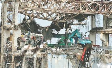 水素爆発で原子炉格納容器のふた(左後方の黄色)もずれた福島第1原発4号機。現在は巨大な鉄骨カバーが覆う=2012年5月