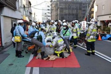 火災現場近くで救護活動をする消防隊員ら=4日午前7時50分ごろ、横浜市中区寿町4丁目