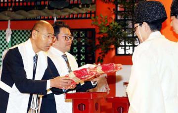 おはらいを受けたたすきを神職(右)から受け取る河野専務理事(左)と下山事務局長(撮影・川村奈菜)