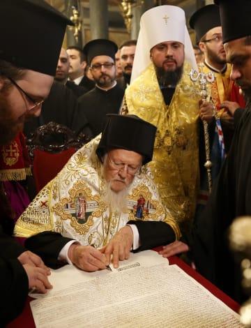 5日、ウクライナ正教会の独立を認める文書に署名するコンスタンチノープル総主教バルソロメオス1世=トルコ・イスタンブール(AP=共同)