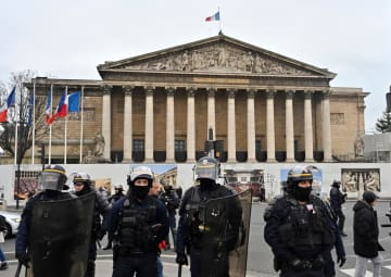 5日、パリの国民議会付近で、黄色いベスト運動のデモに対する警備を固める警官隊(ゲッティ=共同)
