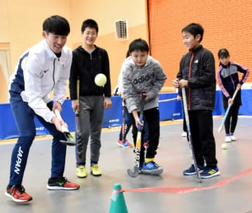 児童にパスの基本を指導する田中海渡選手(左)