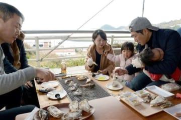 八代海に臨む「オイスターバル」でカキを焼く来場者=津奈木町