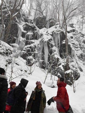 馬門岩の氷柱について、ガイド(右)の説明を受ける観光客ら=5日午後