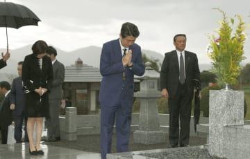 父晋太郎元外相の墓前で手を合わせる安倍首相(中央)。左は昭恵夫人=6日午後、山口県長門市