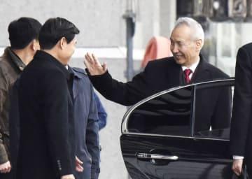北京の中国商務省で見送りに手を振る劉鶴副首相(右)=7日(共同)