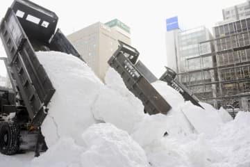 「第70回さっぽろ雪まつり」会場の大通公園にトラックで運び込まれた雪=7日午前、札幌市中央区