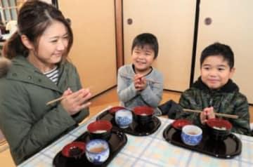 ふるまわれた七草がゆを食べる親子=7日午前10時3分、大分市永興の臨済寺