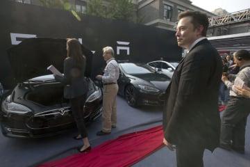 北京でのイベントでテスラ車を眺めるイーロン・マスクCEO(手前右)=2014年4月(AP=共同)