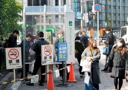 禁煙の看板の近くに設けられた公衆喫煙所。お昼には喫煙者であふれる=神戸市中央区、JR三ノ宮駅前(撮影・後藤亮平)