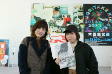 1万人目でプレゼントを受け取った中島令渚さん(右)と早川実里さん=7日、大分市の県立美術館