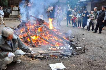 【鏡餅(手前)を焼きながら、かがり火にしめ飾りを投げ入れる参拝者ら=四日市市波木町の加富神社で】