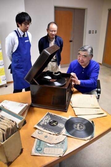 県立図書館で、職員らとSP盤レコードを試聴する田中さん(右)=宮崎市