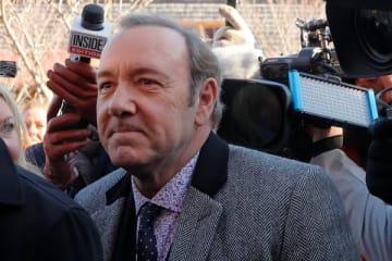 裁判所の入り口で報道陣に囲まれるケヴィン・スペイシー(写真:ロイター/アフロ)