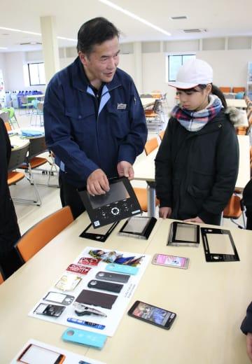 積極的に受け入れる工場見学で、自社製品について説明する従業員(左)