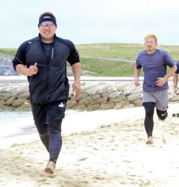 自主トレを公開し、砂浜を走る西武の山川(左)と森=沖縄県宜野湾市