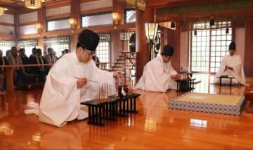竹筒ですくったかゆの米粒を数える権禰宜=伊勢原市大山の大山阿夫利神社