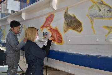 祭事船に魚類や縁起物を描く小川拓哉さん(左)と梅津美幸さん=北茨城市関南町の市漁業歴史資料館「よう・そろー」