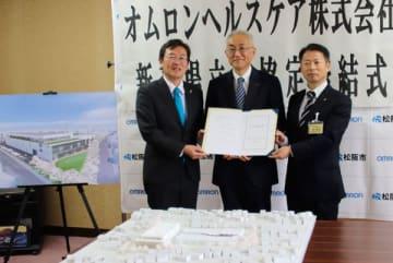 【新工場の模型を前に協定書を示す竹上市長(左)と萩野社長(中央)ら=松阪市役所で】