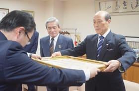 大臣名の表彰状を受け取る中川会長(右)
