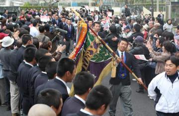 学校関係者や町民が出迎える中、紫紺の優勝旗を掲げて凱旋する清峰高ナイン=佐々町、同校