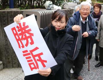 「勝訴」を知らせる原告の弁護士=8日午後1時20分、長崎市万才町の長崎地裁前