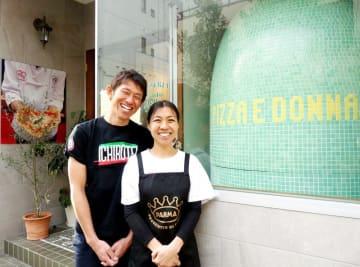 本格ピザ店を切り盛りする吉川さん夫妻。店外からも見えるナポリ製の大きな薪窯が目印だ=市川市