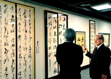 作品を来場者に紹介する豊平主幹(右)=8日、那覇市民ギャラリー