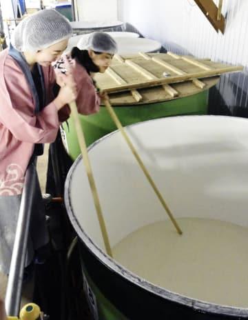 タンクに注ぎ入れた酒米を混ぜほぐす皆生温泉の若おかみら=9日、鳥取県境港市