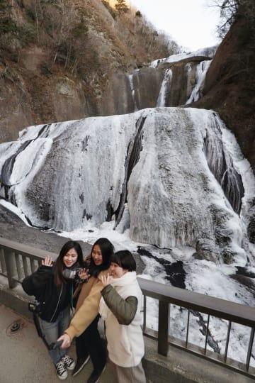 冬の冷え込みで凍結した袋田の滝をバックに記念撮影を楽しむ女性ら=9日午後、茨城県大子町