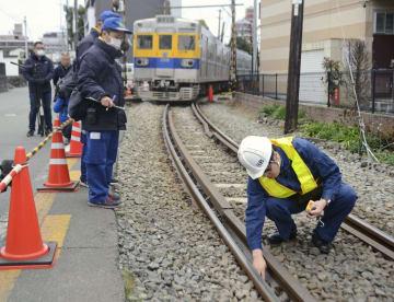 熊本電鉄が脱線した現場を調べる、運輸安全委員会の鉄道事故調査官(右)=9日午後、熊本市