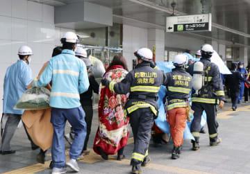 体調不良を訴えた人たちに付き添う消防隊員ら=9日午後2時45分、JR和歌山駅