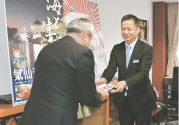 菅原市長(左)に目録を手渡す垣内支社長
