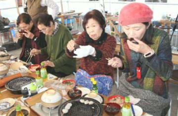 開店と同時に訪れ、ひがた美人の蒸しがきなどを味わう来店客=9日、中津市小祝漁港の「美人小屋」