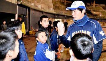 愛媛マンダリンパイレーツの元選手(右)から軟式球の握り方を教わる新居浜市の小学6年生