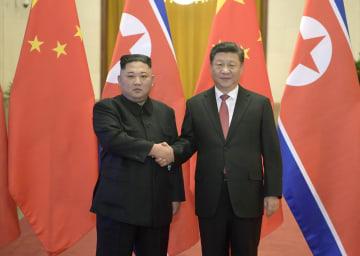 北京の人民大会堂で握手する北朝鮮の金正恩朝鮮労働党委員長(左)と中国の習近平国家主席=8日(新華社=共同)