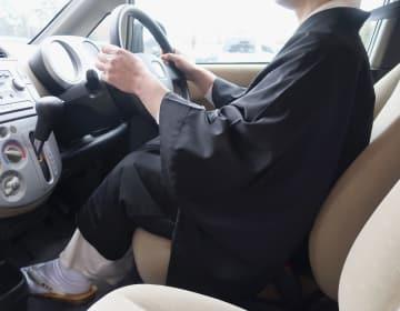 白衣と布袍を着て車の運転席に座る僧侶。仏教界で法事のため僧衣で運転する機会は日常的にあるという=福井市