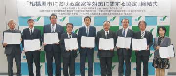 サインした協定書を持つ専門家団体代表者と加山市長