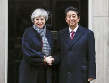 会談前に握手する英国のメイ首相(左)と安倍首相=10日、ロンドン(共同)