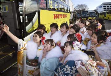 「はとバス」の成人式で記念撮影するバスガイドたち=11日午前、東京都大田区
