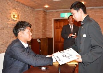 サインした中学生と握手する種市篤暉投手=10日、三沢市